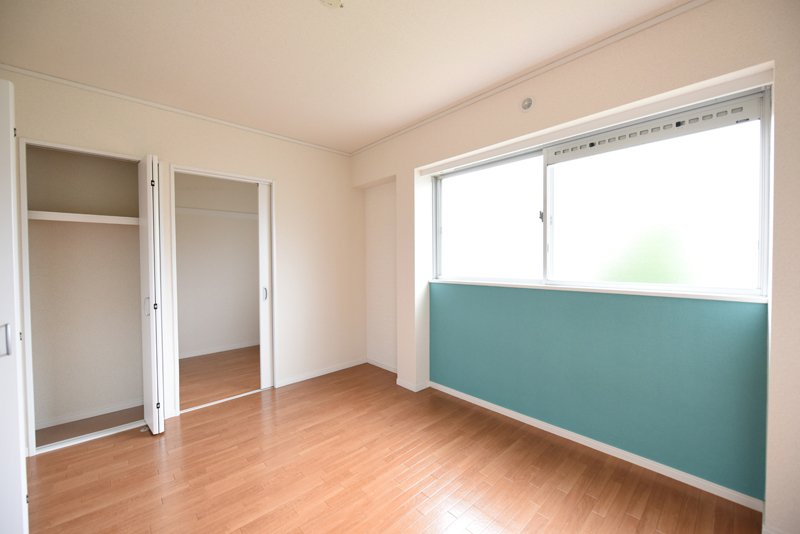 白基調のお部屋にアクセントカラーの壁紙が映える